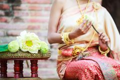 Woman in traditional clothes fold lotus flower petals used in rituals of Buddhism religion. A Lotus represents purity of body. Speech, and mind, floating above royalty free stock photography