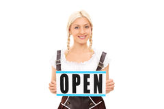 Woman in traditional costume holding an open sign Royalty Free Stock Photography