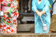 Water purification at entrance of Japanese temple. Woman in traditional dressing kimono takes water for purification at the entrance of Japanese temple Stock Image
