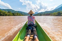 Woman with traditional hat cruising on the brown water of the Nam Ou river in Laos, amazing landscape mountain jungle famous royalty free stock image