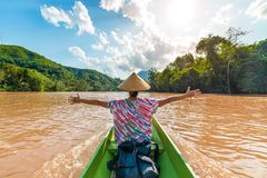 Woman with traditional hat cruising on the brown water of the Nam Ou river in Laos, amazing landscape mountain jungle famous royalty free stock images