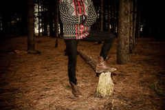 Woman in traditional jumper standing in forest at dusk Royalty Free Stock Photo