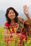 Woman in traditional Nepali costume. Waving in a mustard seed field, focus on hand Stock Photography