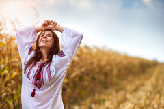 Woman in traditional shirt standing on cornfield. Portrait of a young woman in traditional ukrainian shirt standing with cornfield on the background Royalty Free Stock Image