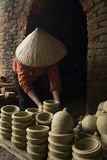 Woman carrying pottery. A woman with a traditional straw hat carrying pottery and a kiln behind her Stock Image