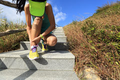 Woman trail runner hold her sports injured ankle Stock Photos