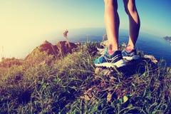 Woman trail runner legs on seaside mountain peak Stock Photos