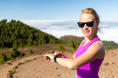 Woman trail runner looking at sport watch Stock Photos