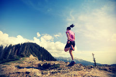 Woman trail runner running on beautiful mountain peak Stock Photos