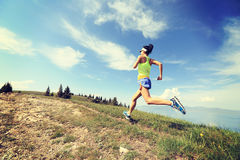 Woman trail runner running on beautiful mountain peak Stock Image
