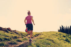 Woman trail runner running on beautiful mountain peak Stock Photo
