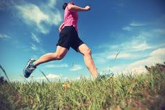 Woman trail runner running on mountain peak Stock Image