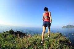 Woman trail runner running on seaside mountain Royalty Free Stock Photos