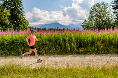 Woman trail running on country road in mountains, summer day. Young woman running in mountains on summer sunny day. Female athlete trail runner on country road Stock Images