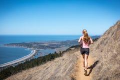 Woman trail running near ocean. Stock Photo