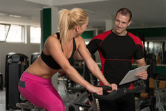 Woman Train Bicycle On Machine With Personal Trainer Royalty Free Stock Photo