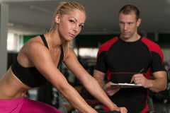 Woman Train Bicycle On Machine With Personal Trainer Stock Photo