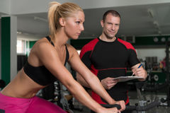 Woman Train Bicycle On Machine With Personal Trainer Royalty Free Stock Photos