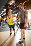 Woman train in gym with trainer assisting royalty free stock image