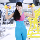 Woman train her biceps at gym center Stock Image