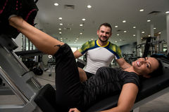 Woman Train Legs On Machine With Personal Trainer Royalty Free Stock Photography
