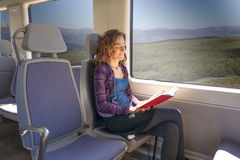 Woman in train reading book Stock Image