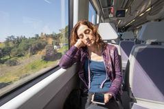 Woman in train sleeping with mobile phone in hands Royalty Free Stock Photos