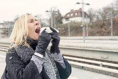 Woman at train station having a cold Stock Photography