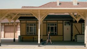 Woman is at the Train Station with Luggage Departing to Holiday Summer Journey. Slender Woman with Luggage is at the Beautiful Train Station in a Small Town stock footage