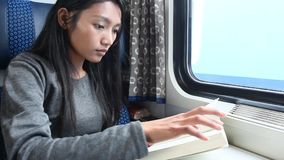 Woman in train. Young woman read her book while traveling by train stock video