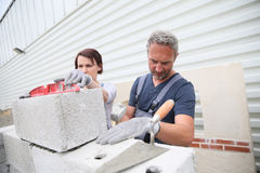 Woman trainee laying bricks with instructor Royalty Free Stock Images
