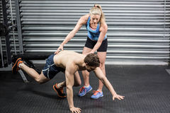 Woman trainer assisting man. Woman trainer assisting men  at crossfit gym Stock Photo