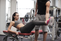 Woman with trainer doing abdominal exercise in gym Stock Images
