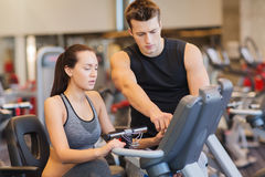 Woman with trainer on exercise bike in gym Royalty Free Stock Photos