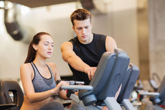 Woman with trainer on exercise bike in gym Stock Photos