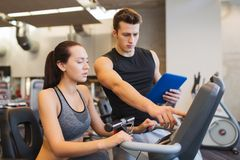Woman with trainer on exercise bike in gym Royalty Free Stock Images