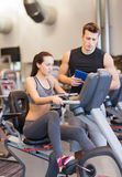 Woman with trainer on exercise bike in gym Stock Photography