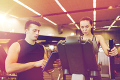 Woman with trainer exercising on stepper in gym Stock Image