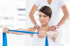 Woman with trainer holding resistance band Stock Image