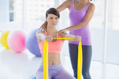Woman with trainer holding resistance band Stock Photos