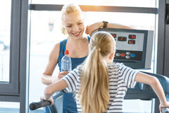 Woman trainer looking at small girl workout on treadmill Stock Image