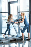 Woman trainer looking at small girl workout on treadmill Royalty Free Stock Photos
