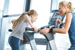 Woman trainer looking at small girl workout on treadmill Stock Photos
