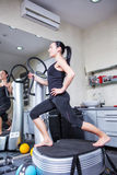 Woman on trainer machine in sport gym Stock Images