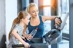 Woman trainer with small girl workout on treadmill Royalty Free Stock Images