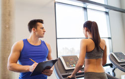 Woman with trainer on treadmill in gym Stock Images