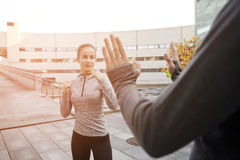 Woman with trainer working out self defense strike. Fitness, sport, people, exercising and martial arts concept - young women with trainer working out self Royalty Free Stock Images