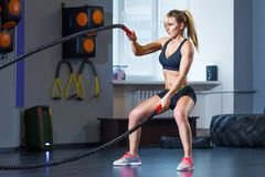 Woman training with battle rope in cross fit gym stock image