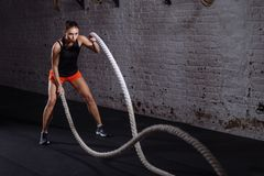 Athletic woman doing battle rope exercises at gym. Woman training with battle rope in cross fit gym Royalty Free Stock Images