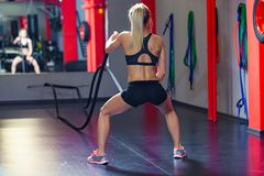 Woman training with battle rope in cross fit gym. back view royalty free stock photography